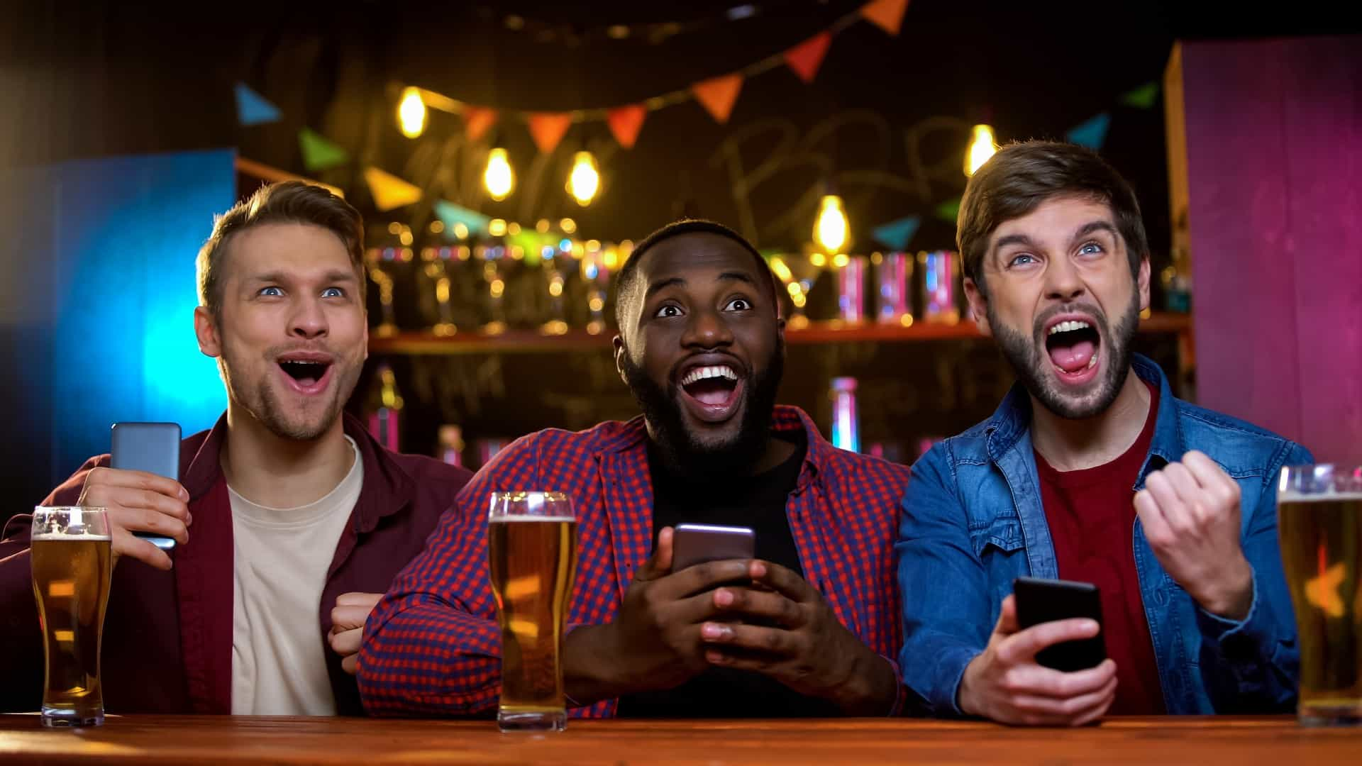 3 men at bar betting on sports online 16.9