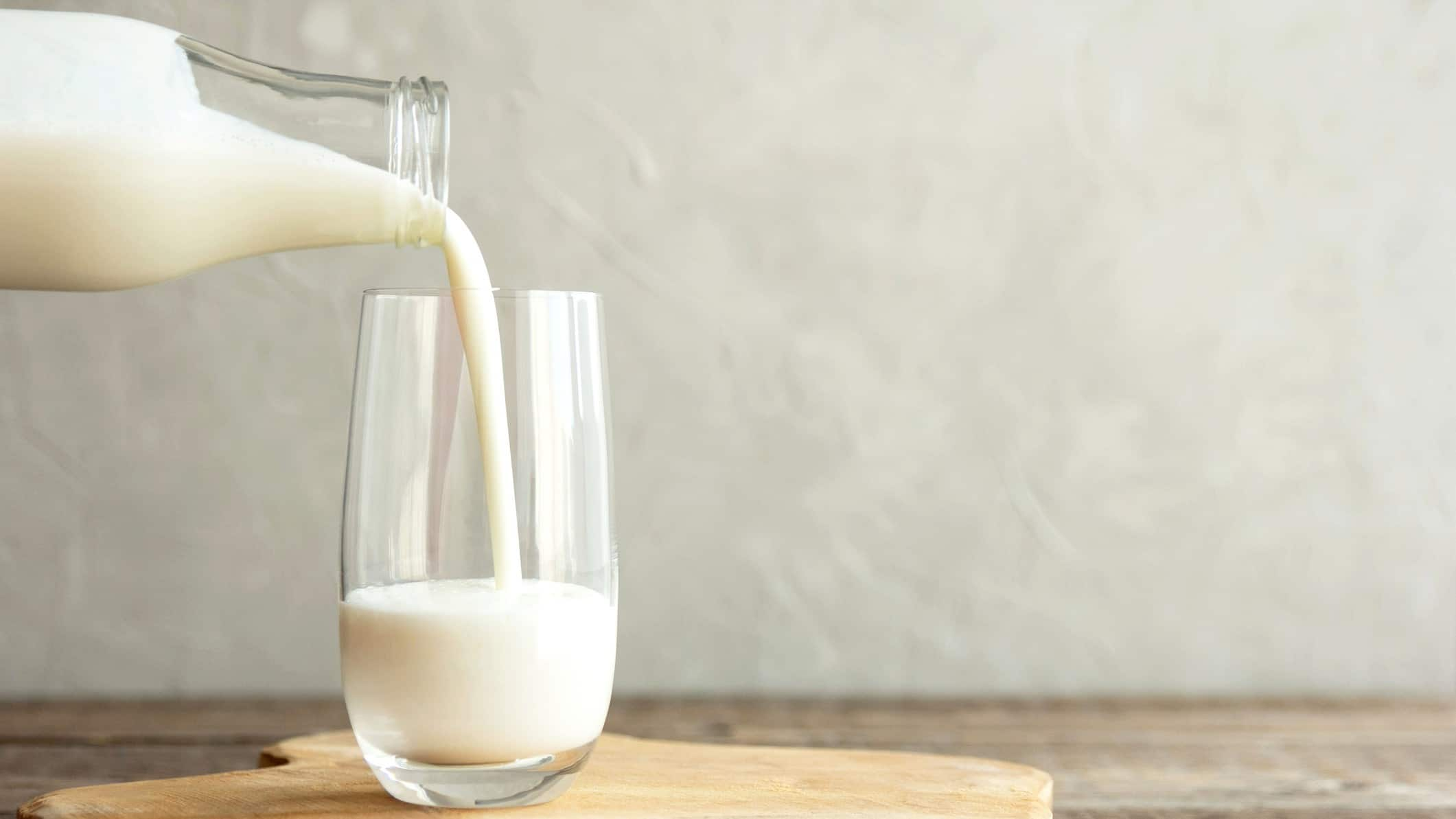pouring glass of milk from glass milk bottle