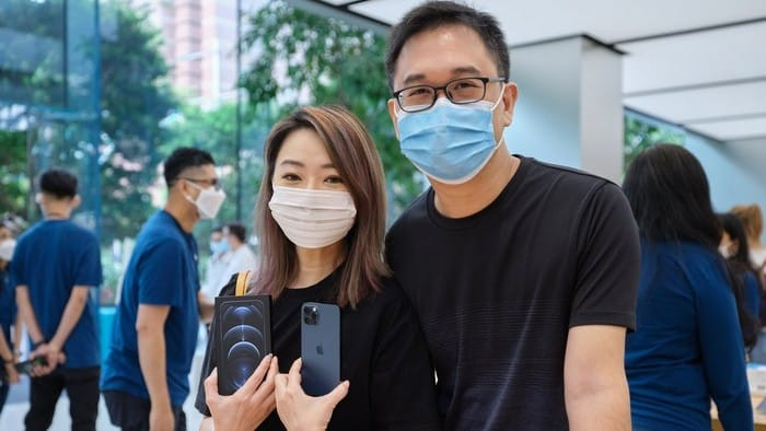 Man and woman in blue face masks hold up Apple iPhones in an Apple store