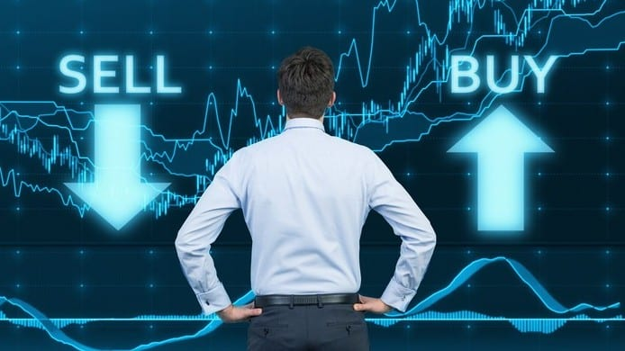Businessman with hands on hips looks at share price chart with the words 'buy' and 'sell '