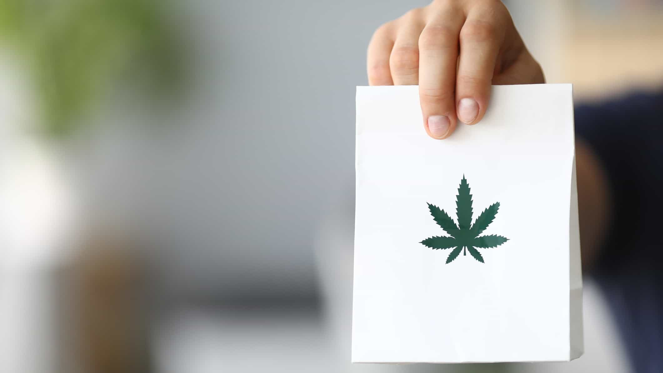 ASX Cannabis share price represented by asx investor holding card with cannabis leaf on it