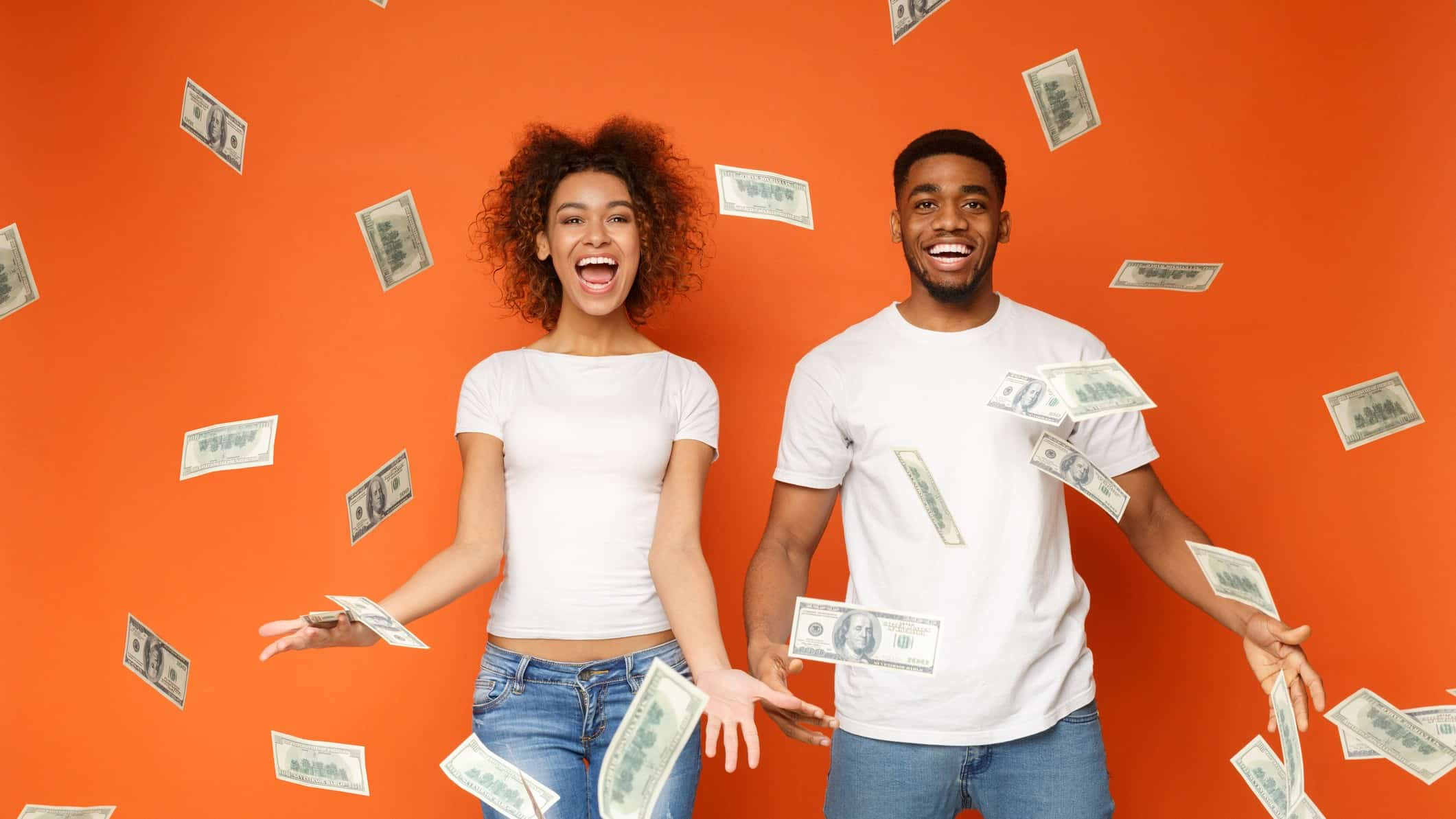 Happy young man and woman throwing dividend cash into air in front of orange background