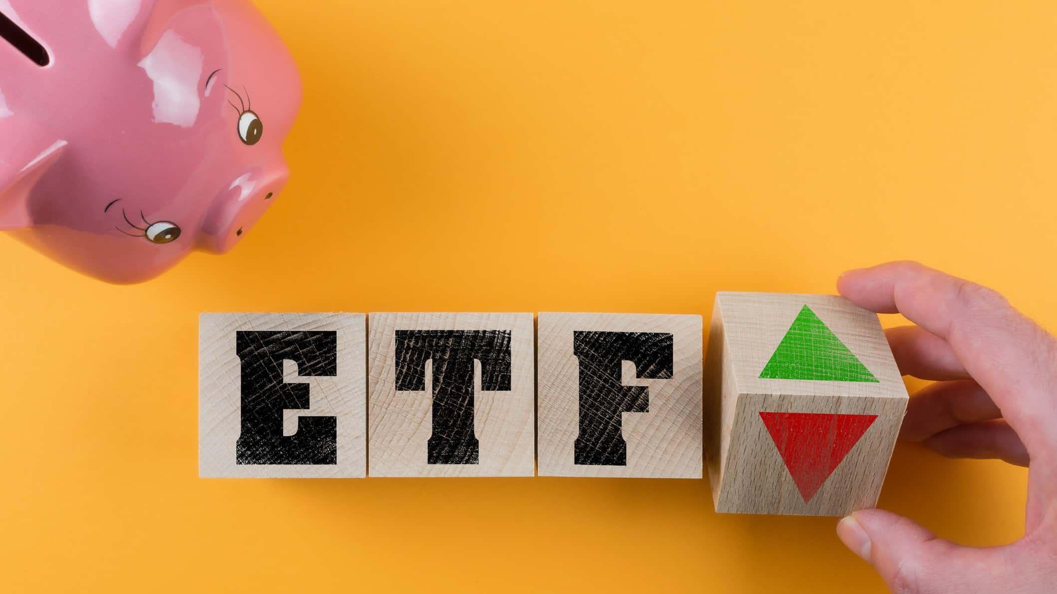 Block letters 'ETF' on yellow/orange background with pink piggy bank