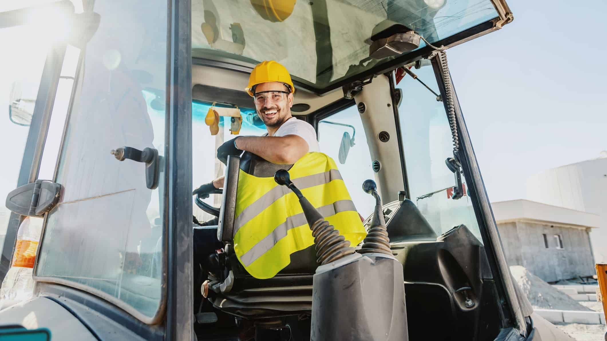 male wearing high vis vest smiling while sitting in excavator cabin