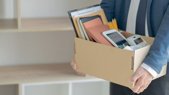 Man in business suit carries box of personal effects