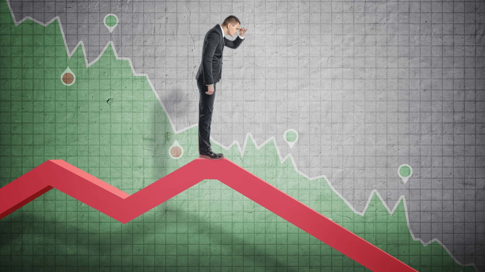 man looking down falling line chart, indicating a falling share price