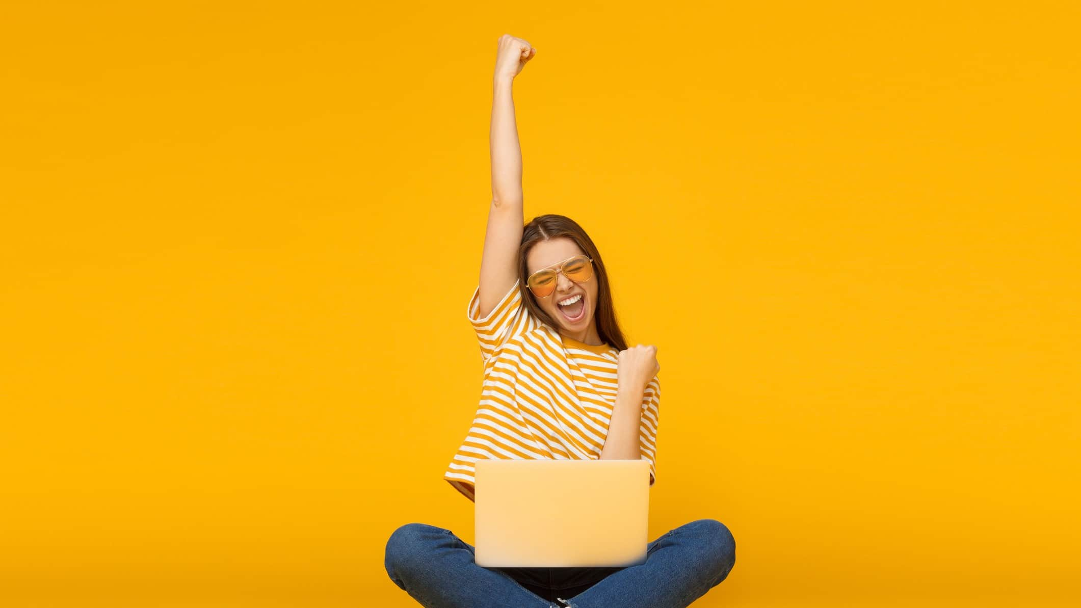 Young woman in yellow striped top with laptop raises arm in victory