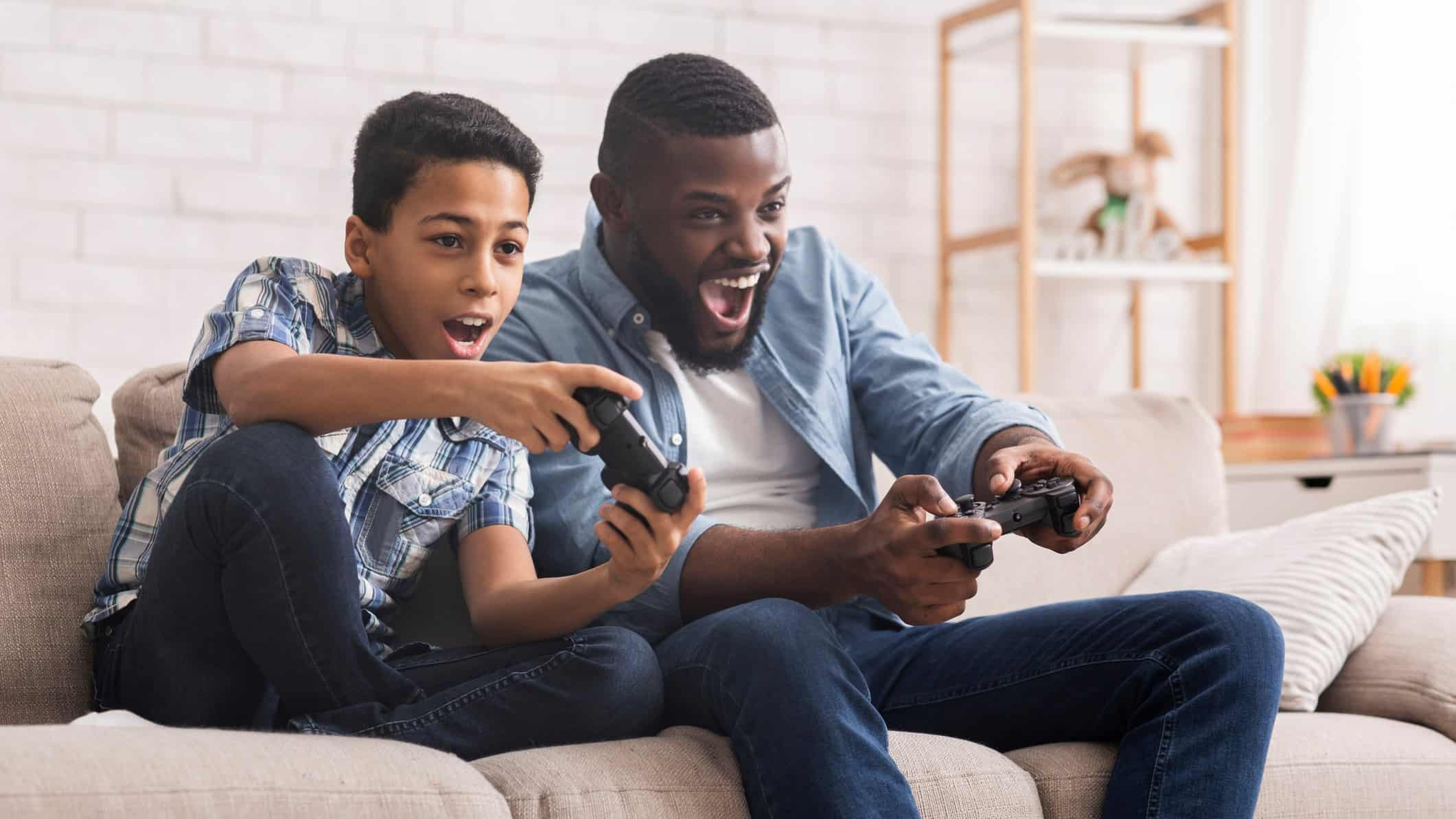 Cheerful Father And Son Competing In Video Games At Home