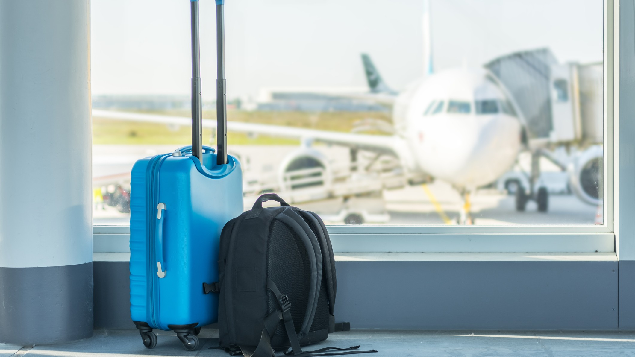 Travel bags sit by an airport lounge window overlooking a grounded plane on the tarmac