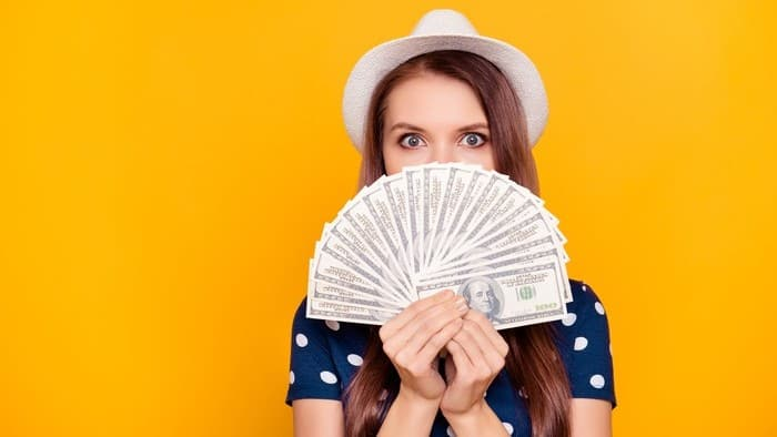 Young female investor holding cash