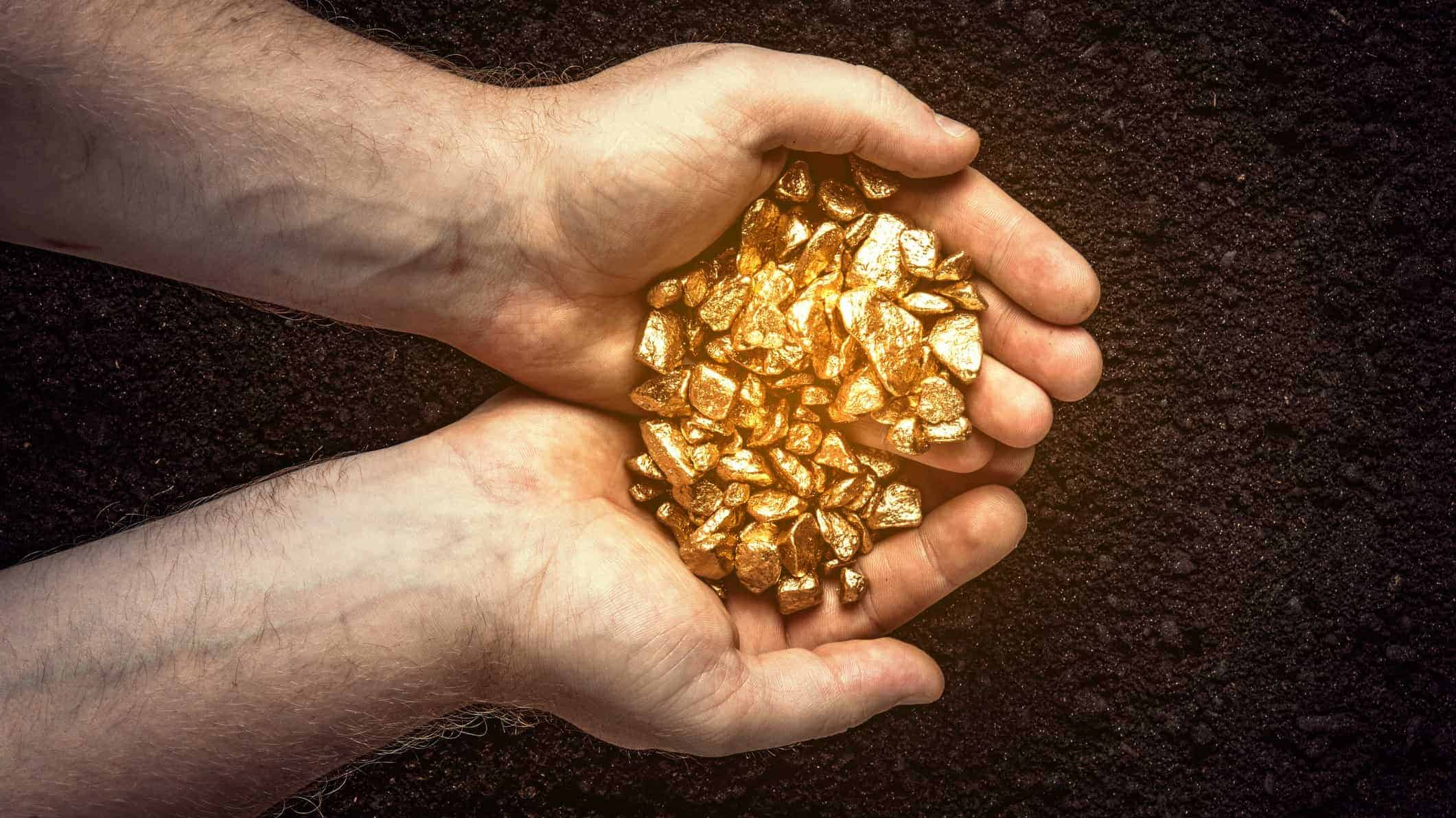 gold asx share price rise represented by hands holding pile of gold