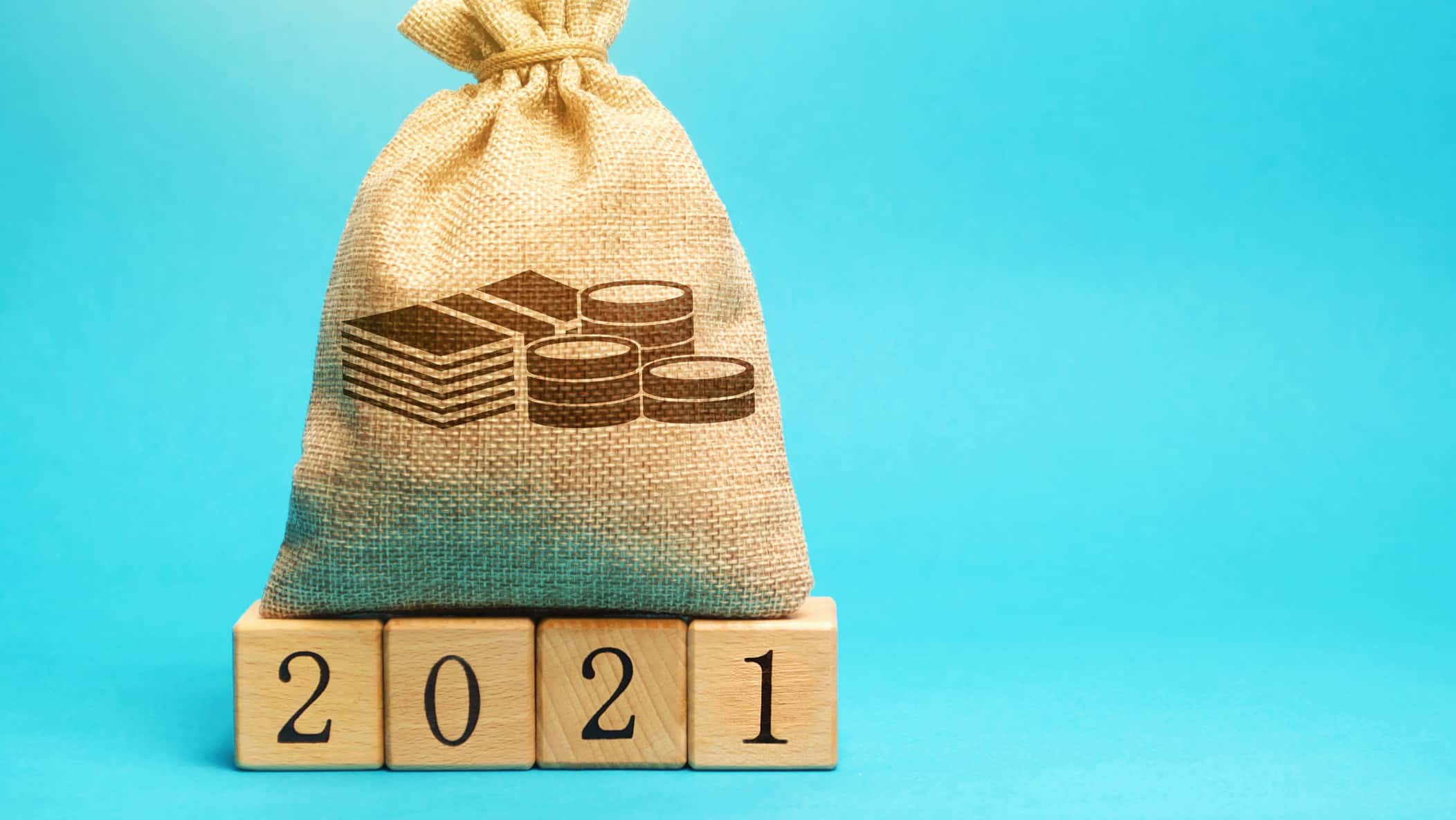 Bag of money sitting on top of wooden blocks spelling out 2021