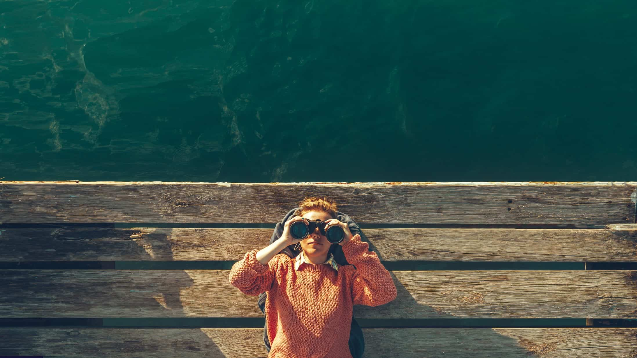 Woman in pink sweater lying on dock with binoculars to her eyes