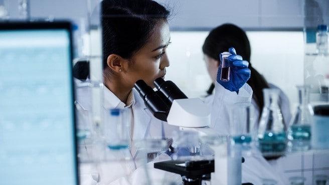 Female scientist in lab examines coronavirus vaccine