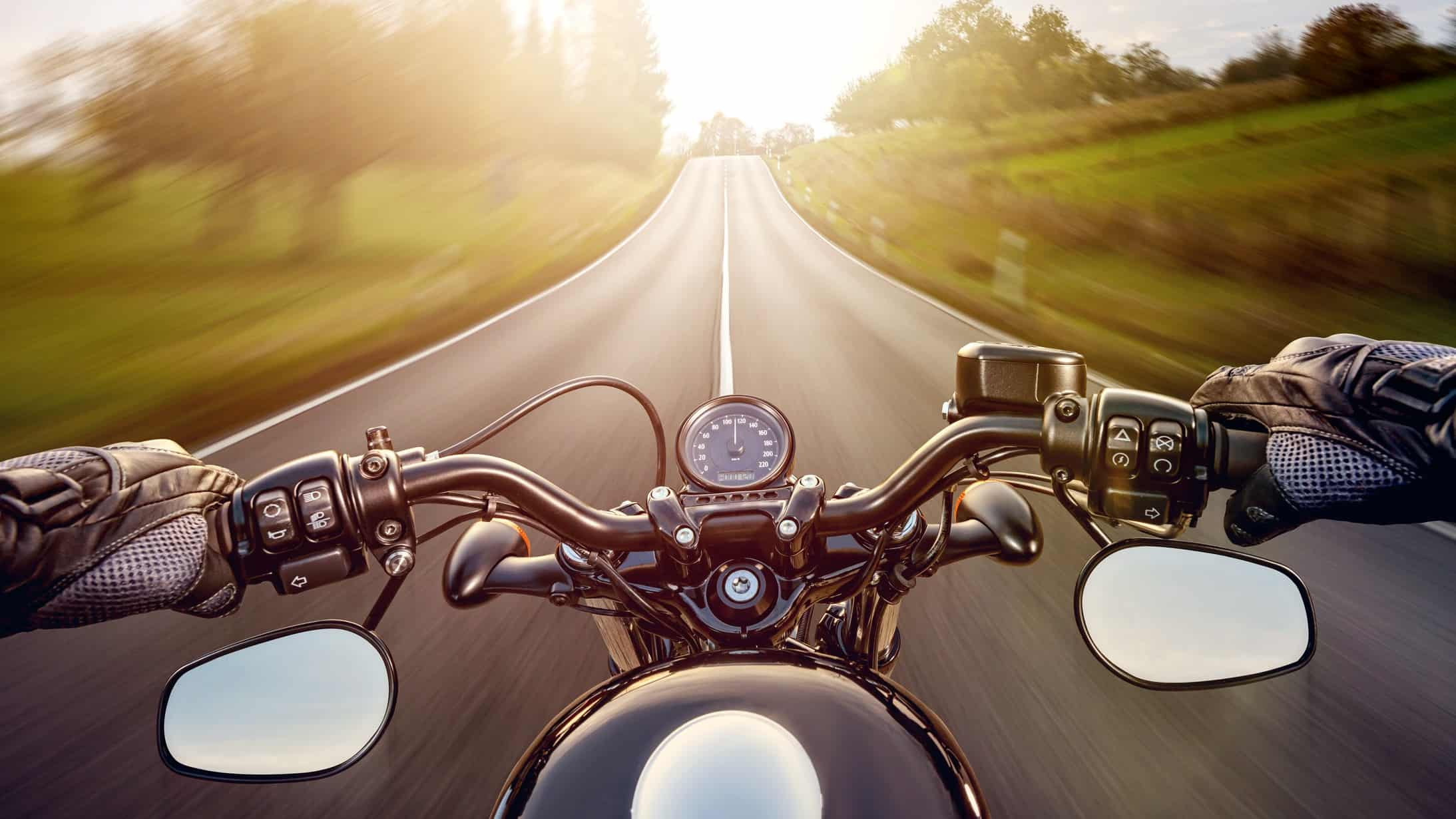 Photo from motorcycle rider's perspective looking at handlebars and road with green fields either side