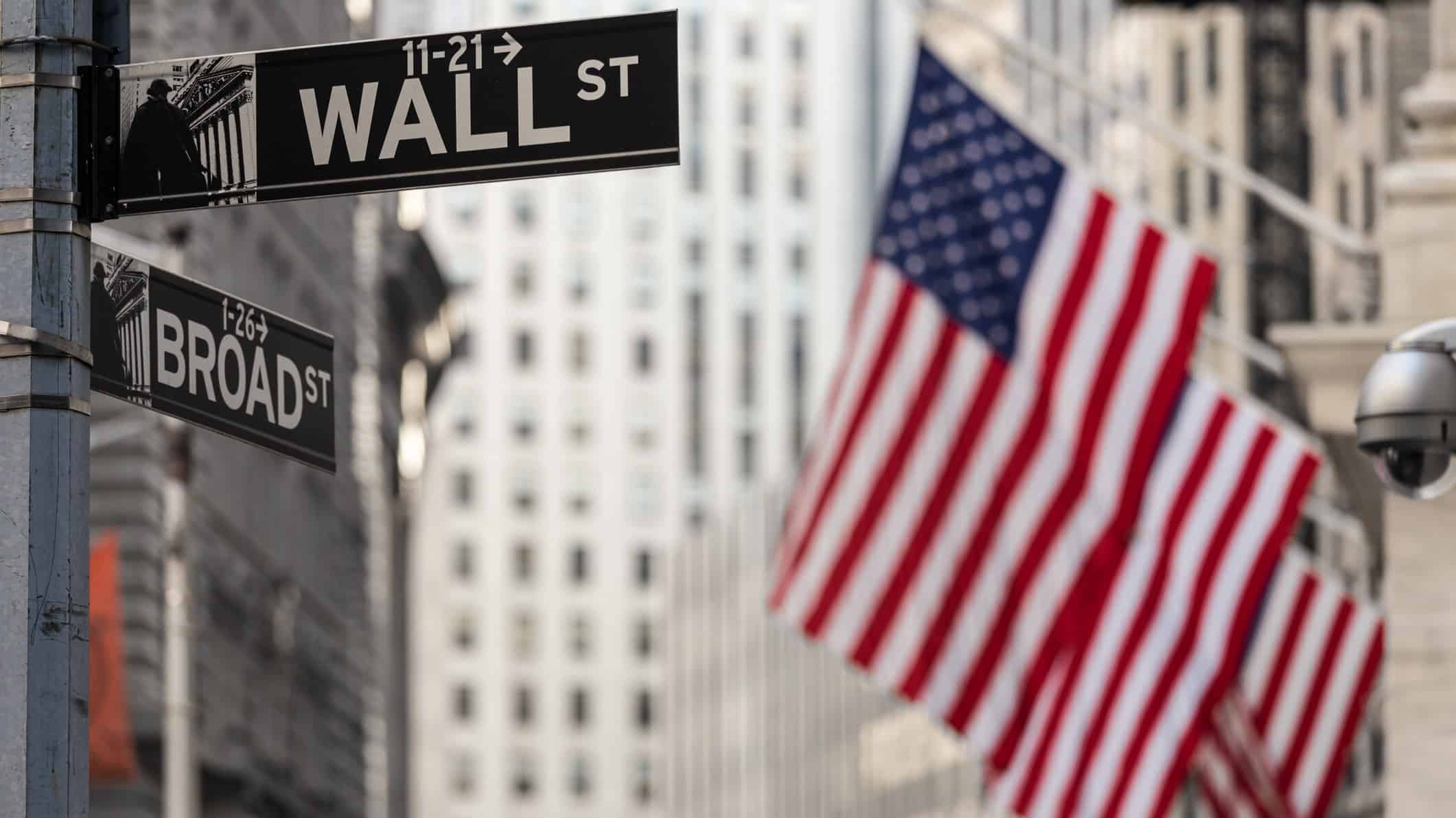 Road sign for 'Wall St' with US flags in background