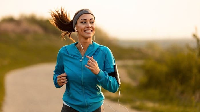 A female dressed in sports gear smiles as she runs along a road, indicating a positive share price for sports apparel companies