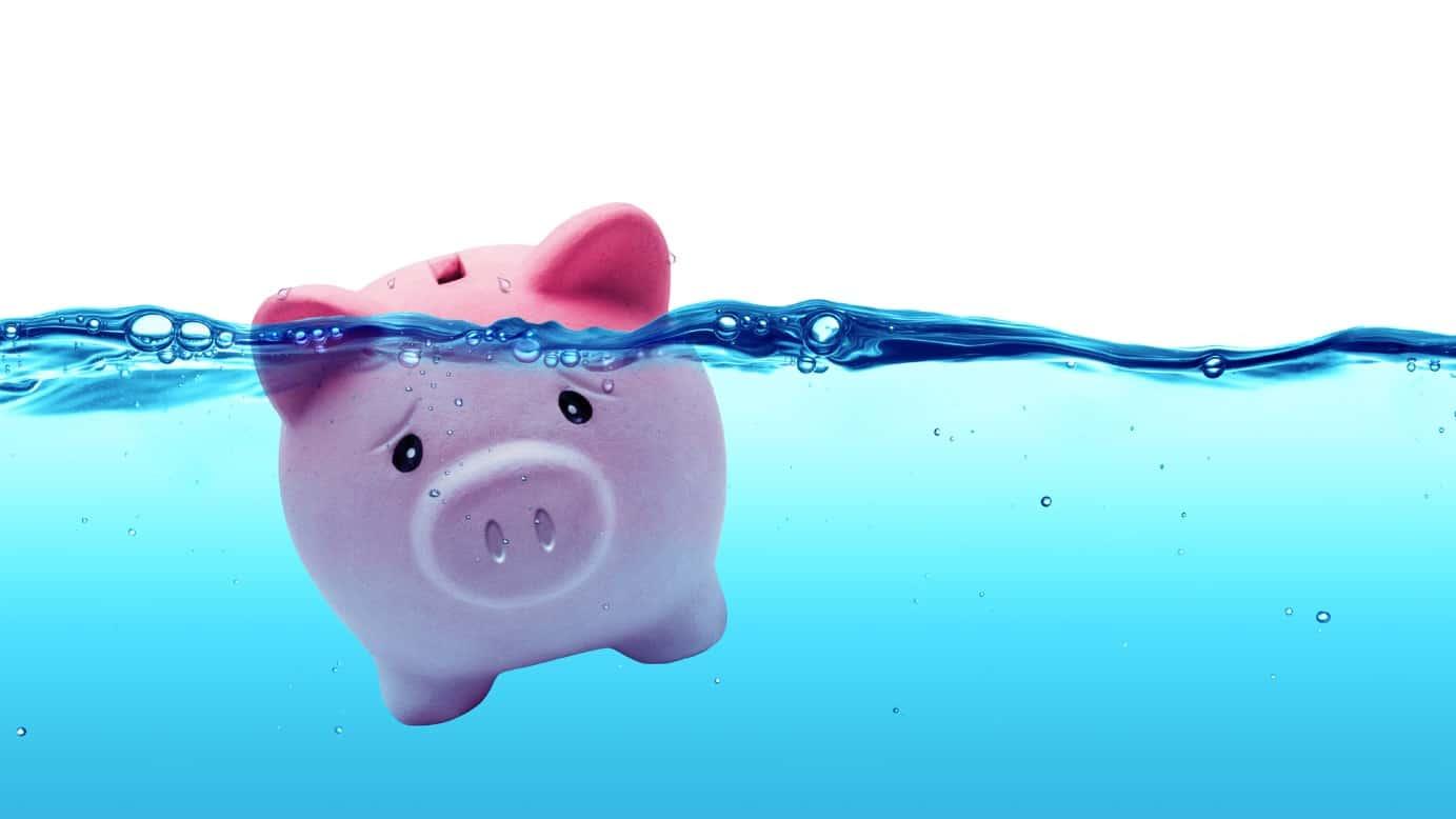sad piggy bank sinking underwater