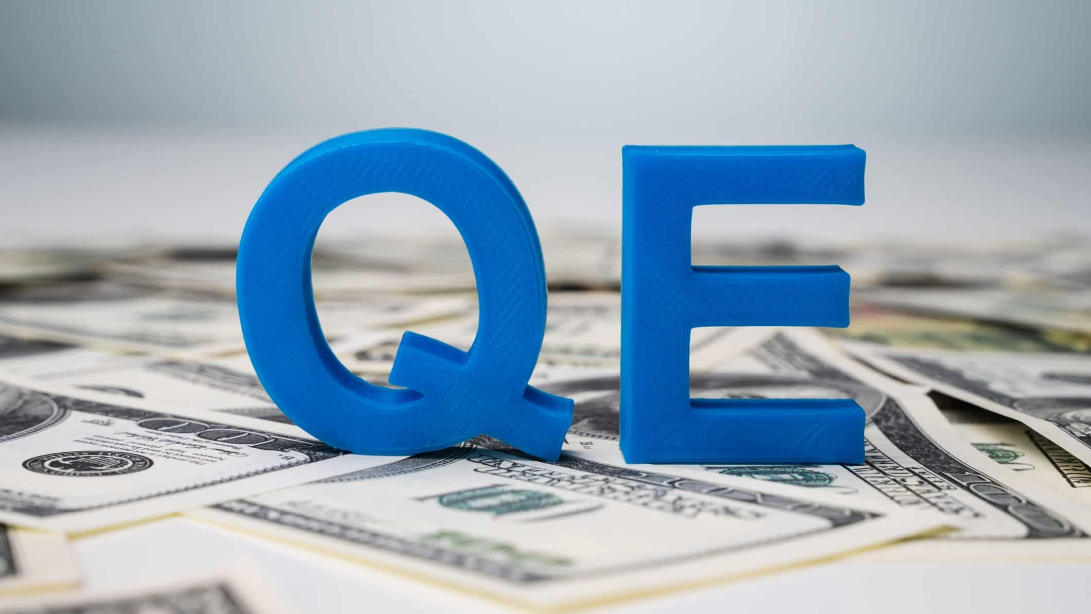 quantitative easing represented by letters QE sitting on piles of cash