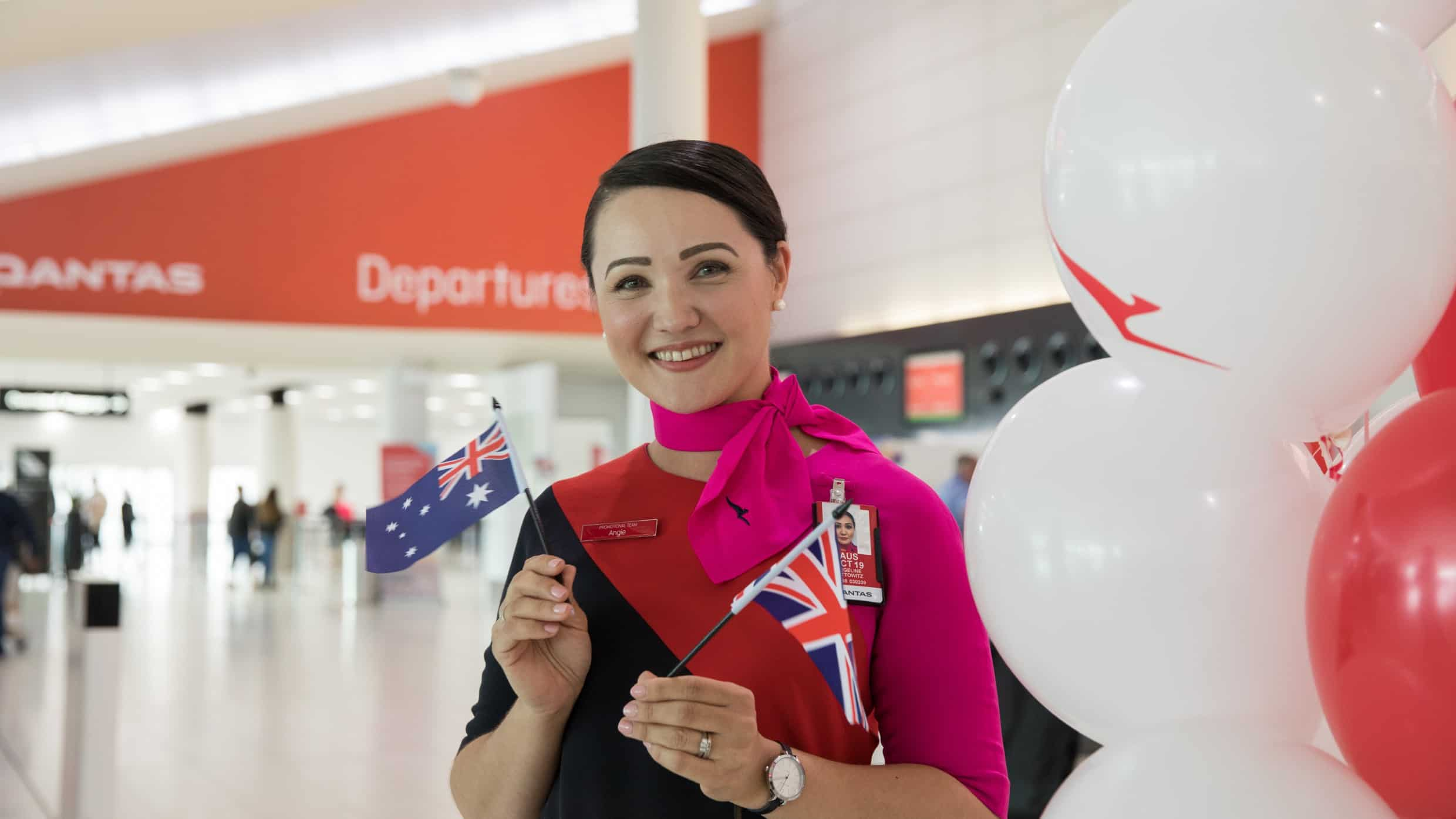 Female Qantas staff member holding AU and English flags in airport departure lounge