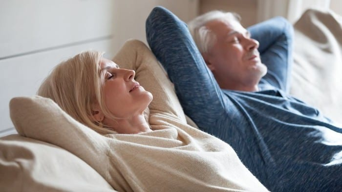 Retired couple reclining on couch with eyes closed