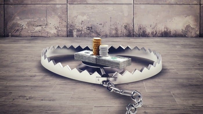 Cash piled up in the middle of a bear trap symbolising risky investments