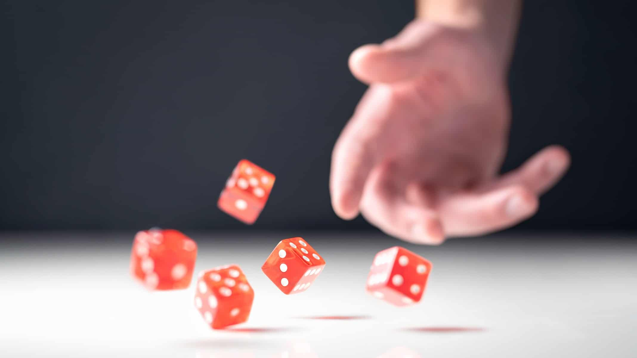 Hand throwing four red dice