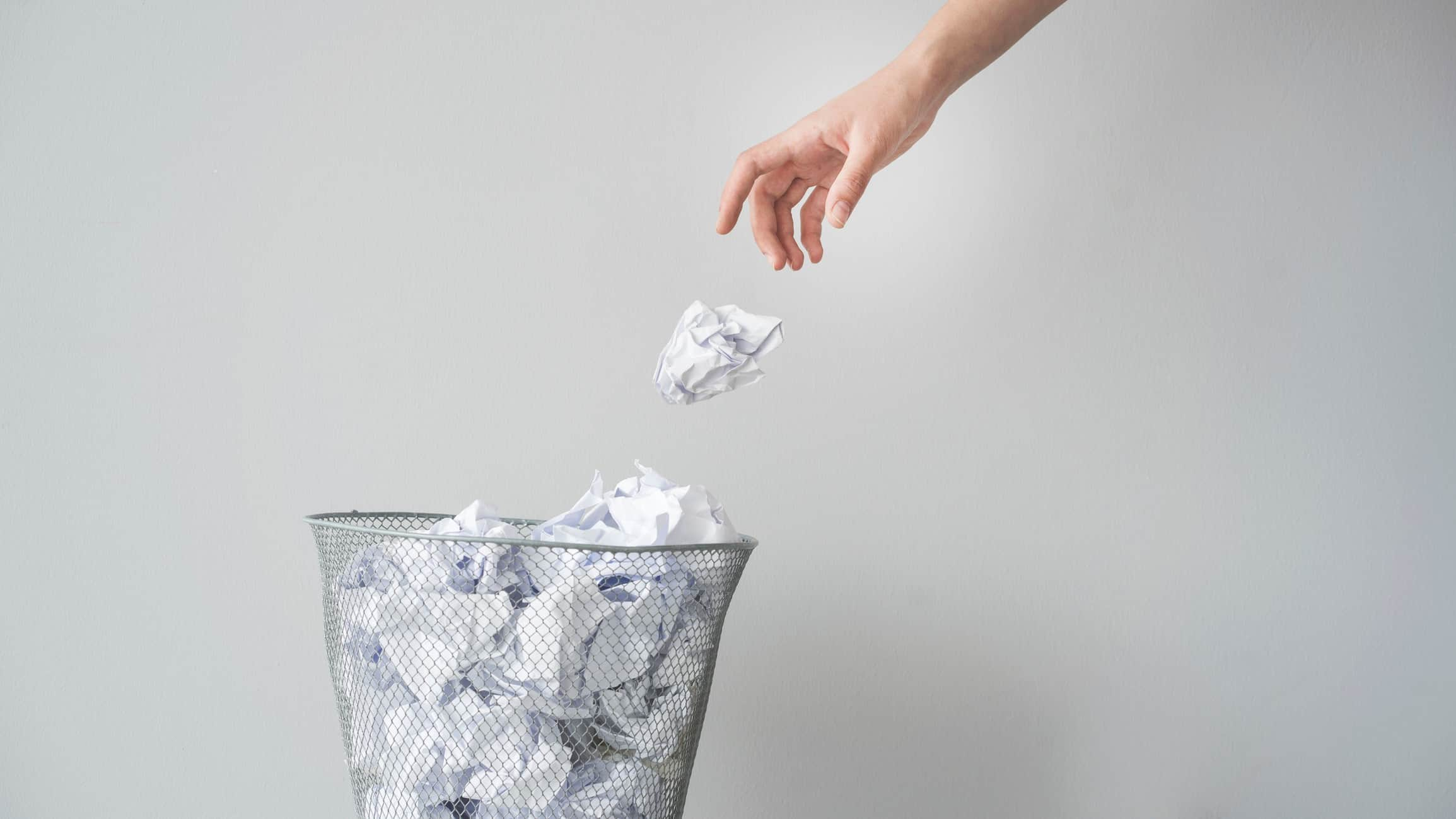Hand throwing scrunched up paper in rubbish bin