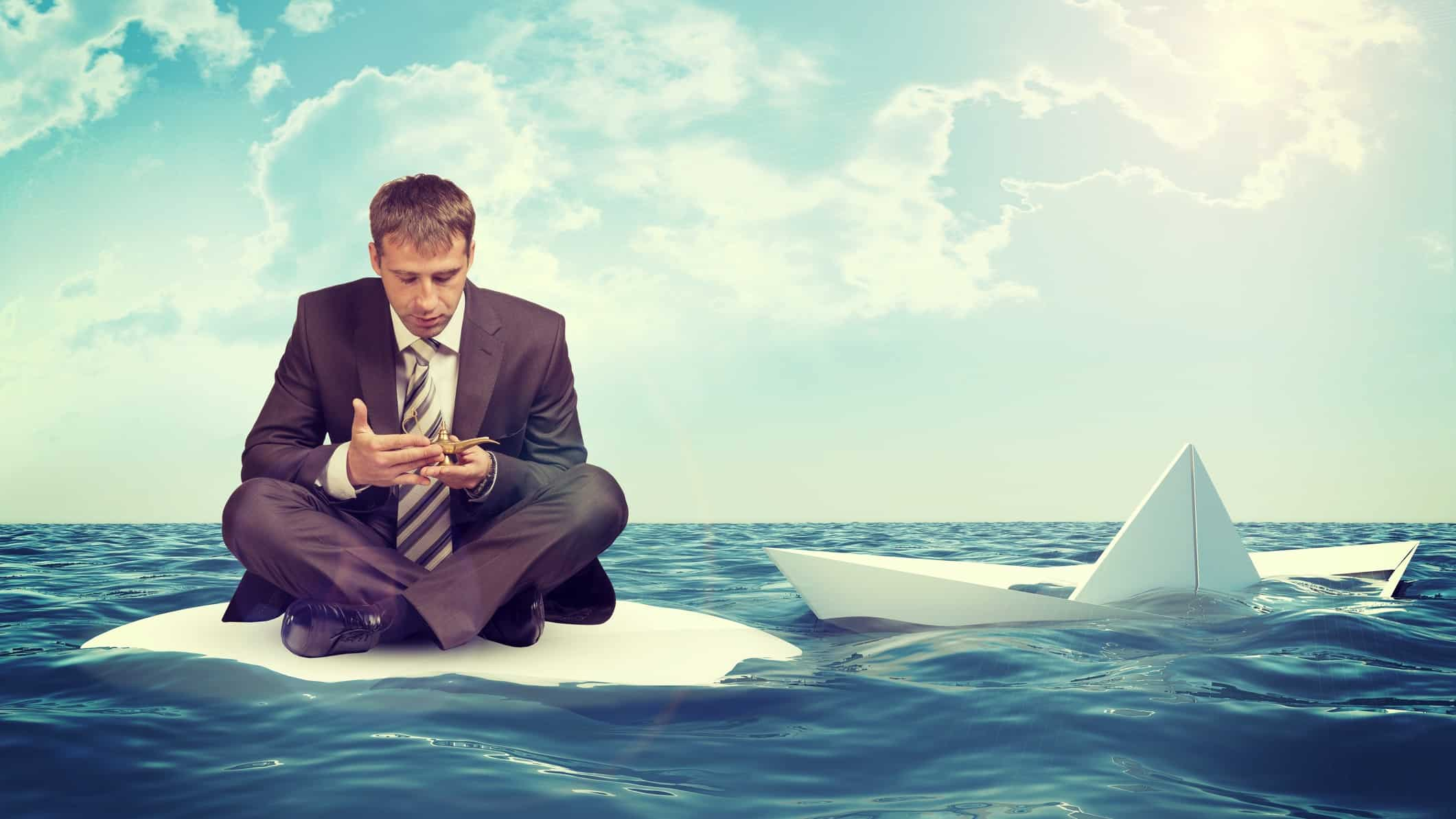 Man in business suit sits on sinking raft while looking at phone