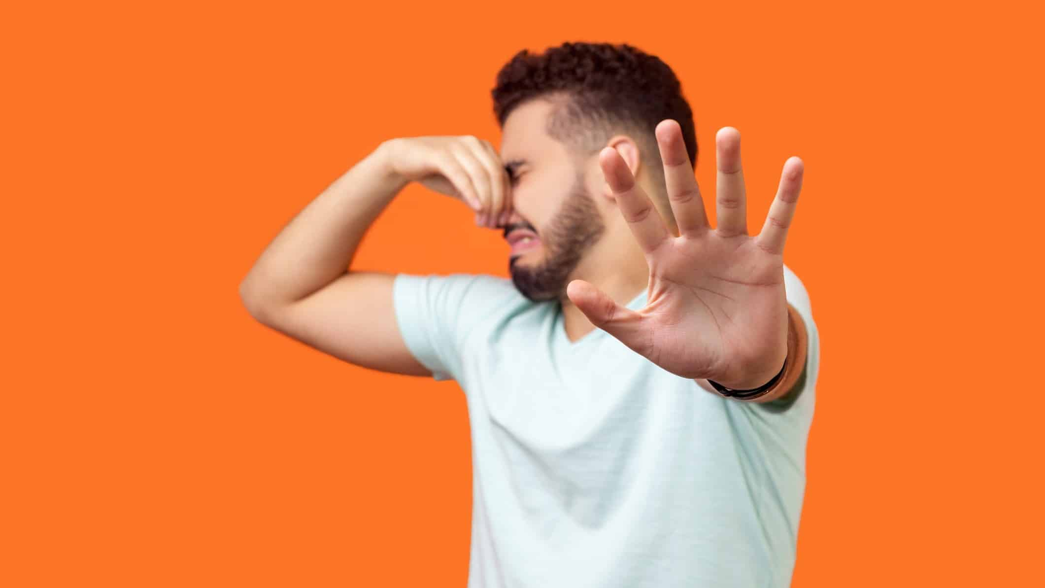 Man pinching nose and holding other hand up in a 'stop' gesture turning away in front of an orange background