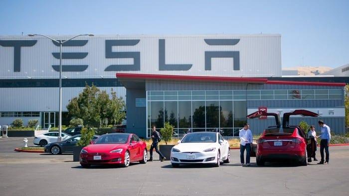 Tesla vehicles parked in front of Tesla building