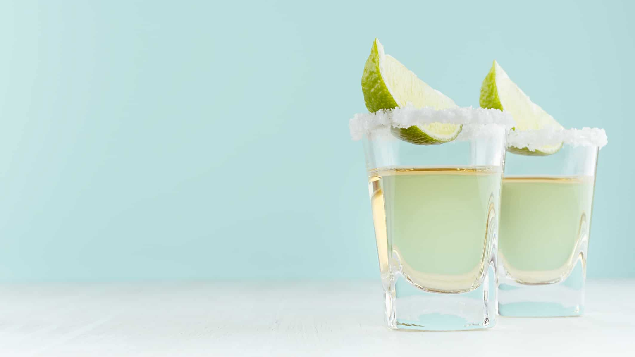 Two shot glasses with tequila, salt and lime on a light blue background