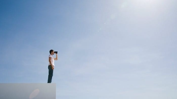 Man with binoculars standing on edge of building looking into distance