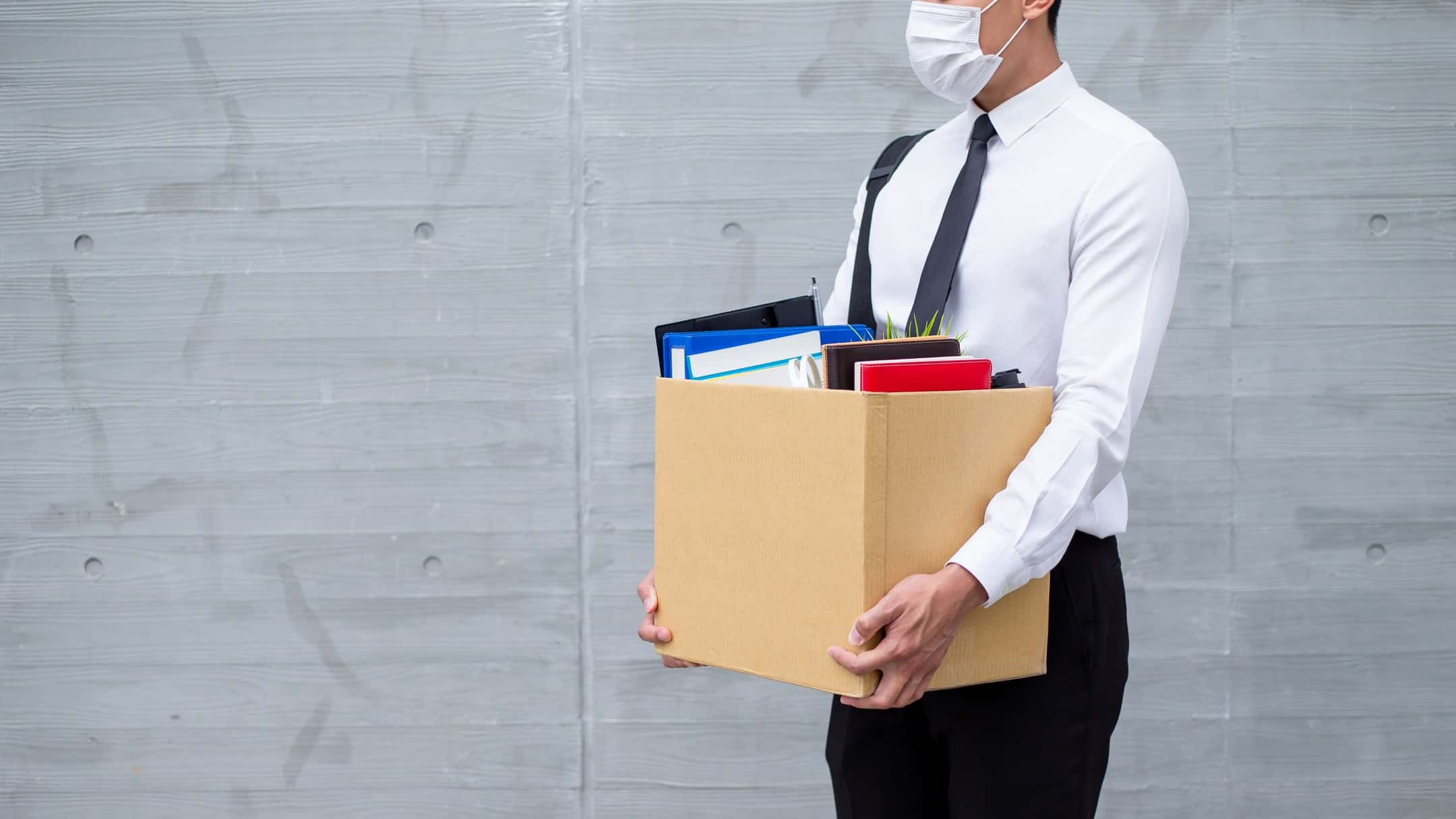 Recently unemployed man in white business shirt wearing face mask carrying box of belongings