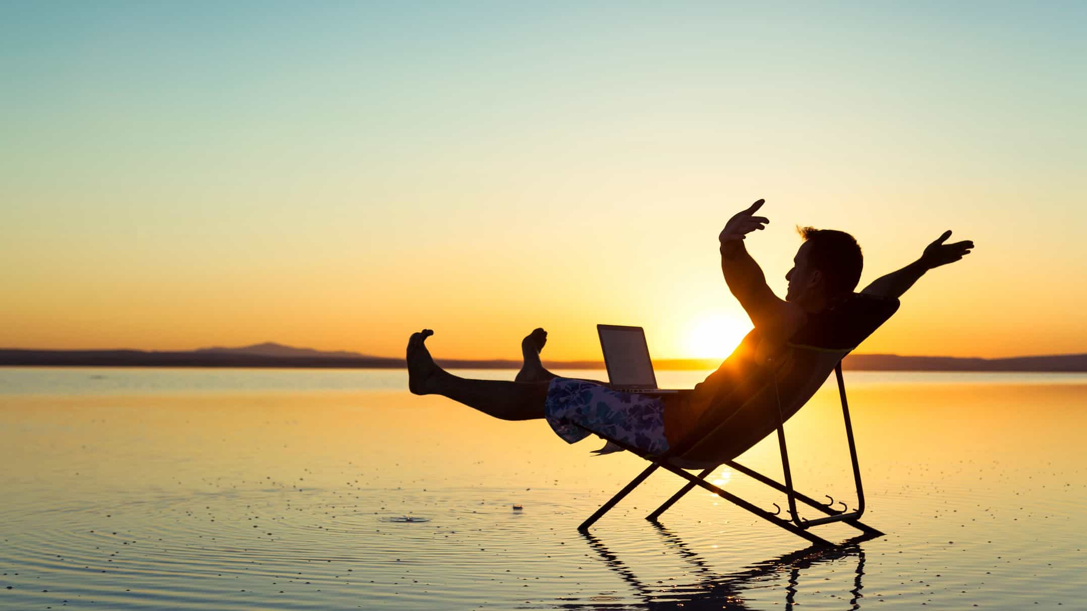 Man in deck chair on a beach at sunset with laptop and arms outstretched
