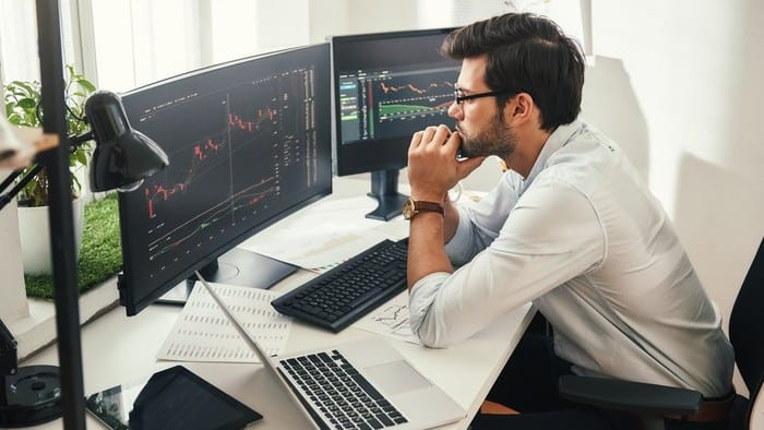 Worried young male investor watches financial charts on computer screen