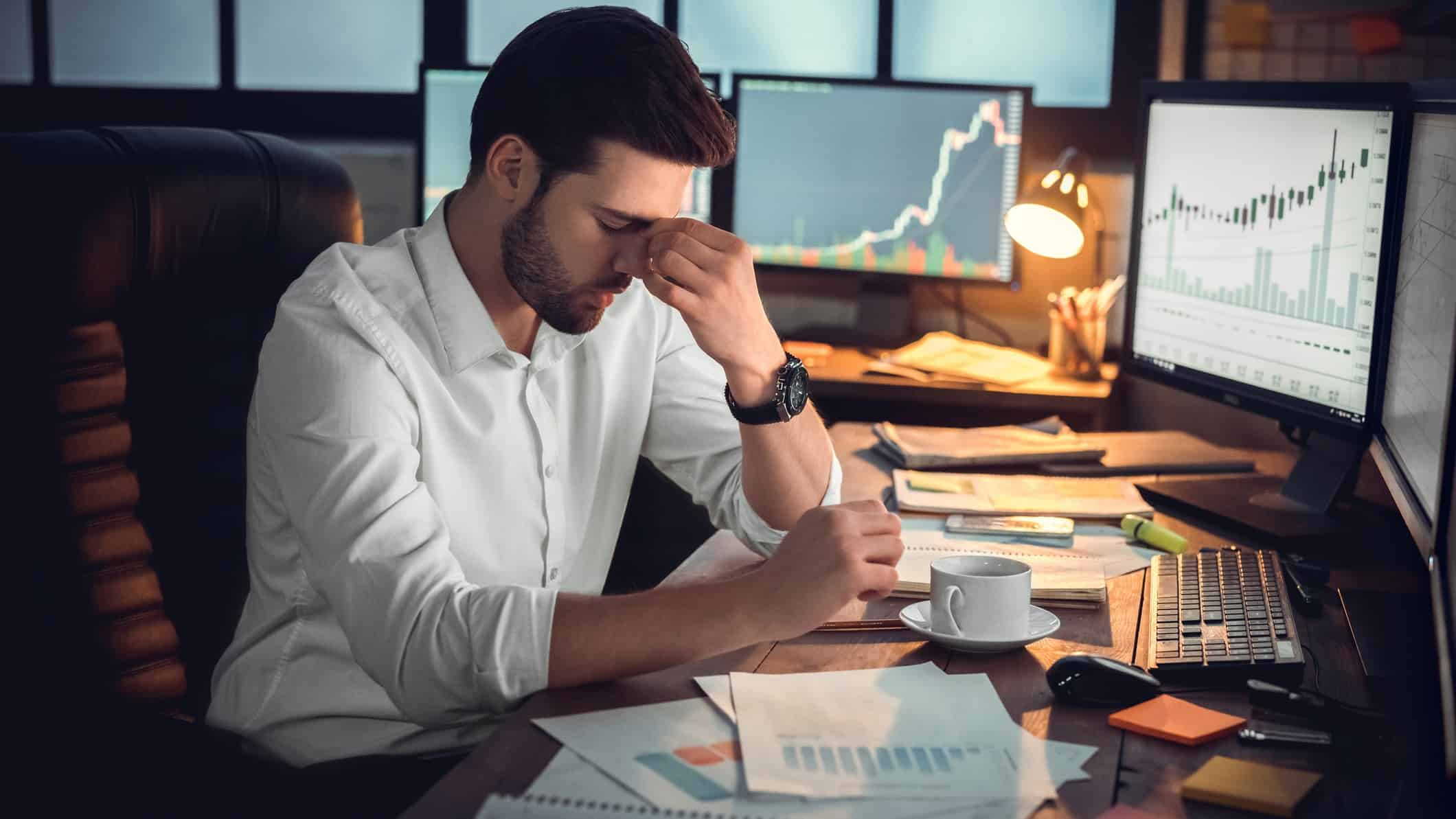 businessman sitting at desk with head in hands in front of computer screens with falling financial charts, asx recession