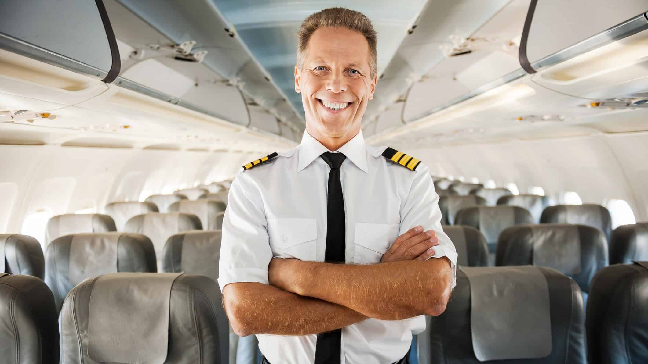 rising airline asx share price represented by happy pilot standing inside empty plane