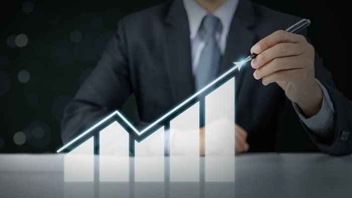 man drawing rising line graph representing increasing apple stock