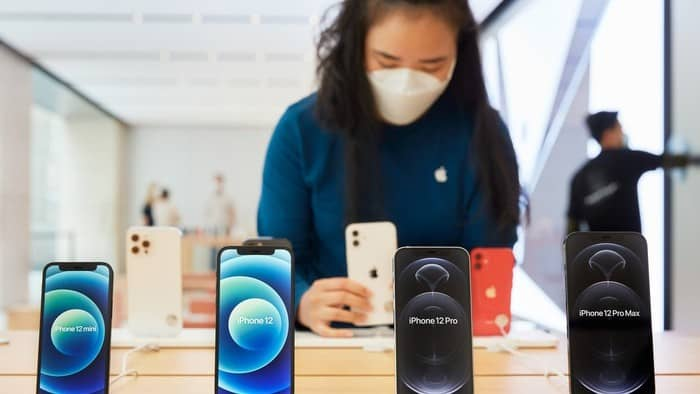 Falling Apple stock price represented by woman wearing face mask looking at products in Apple store