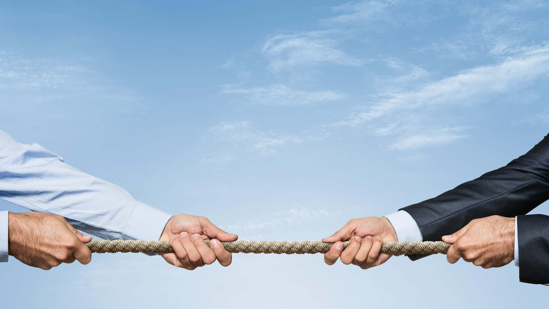 asx shares asset sales and mergers and acquisitions represented by two business men playing tug of war with rope