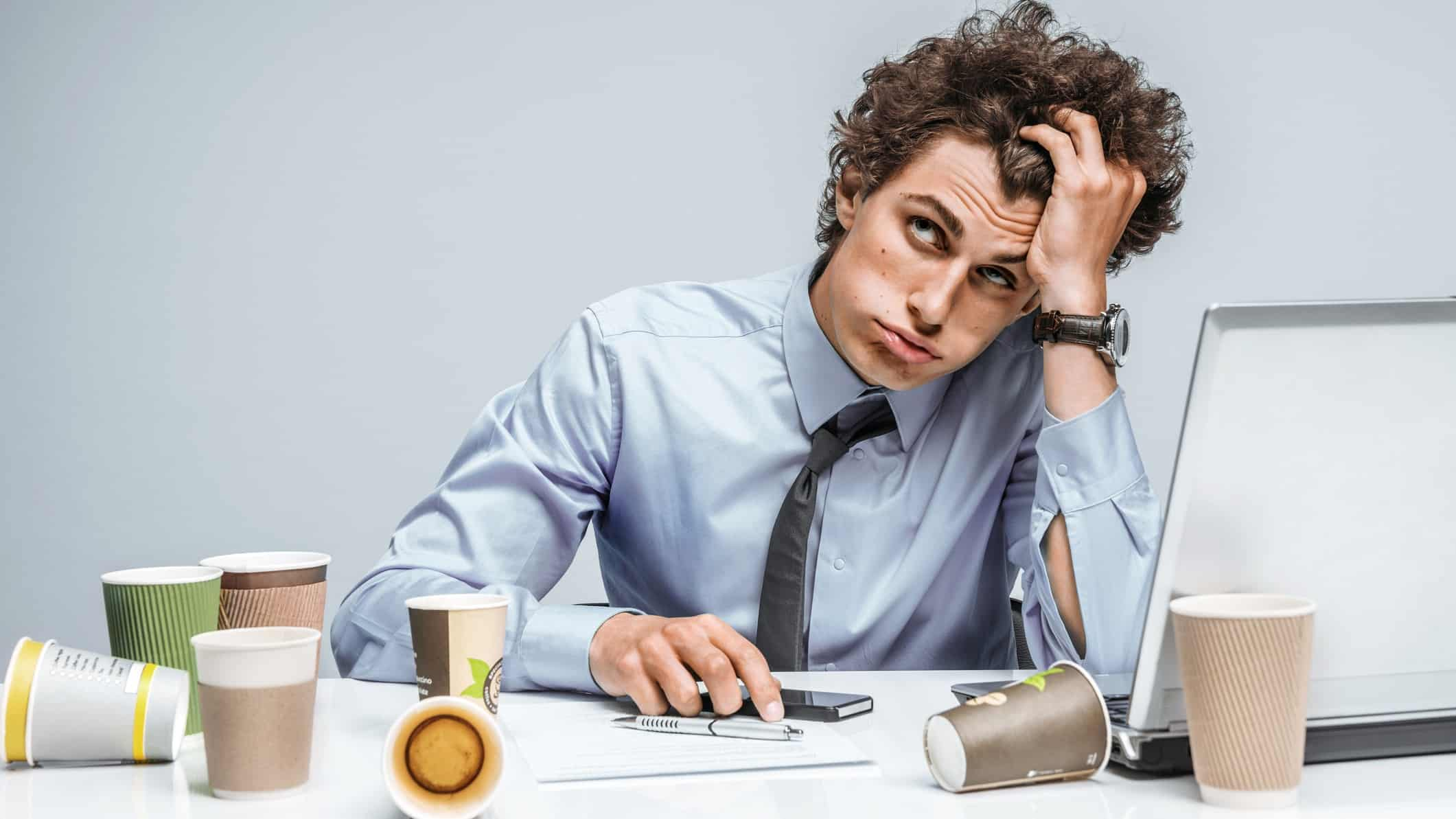 business man looking tired and frustrated at desk surrounded by empty coffee cups
