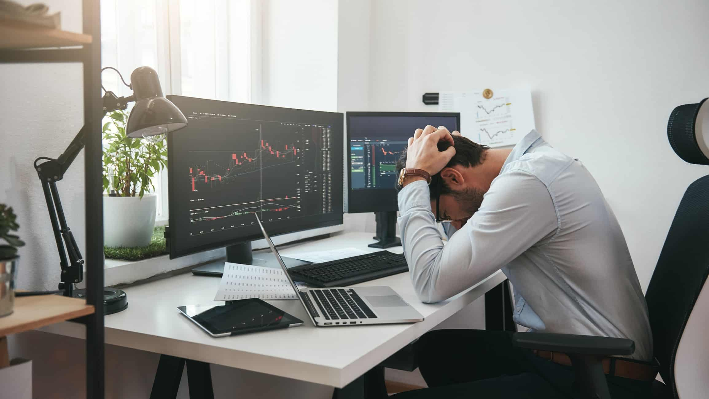 man with head in hands after looking at stock market crash on computer, asx 200 share market crash