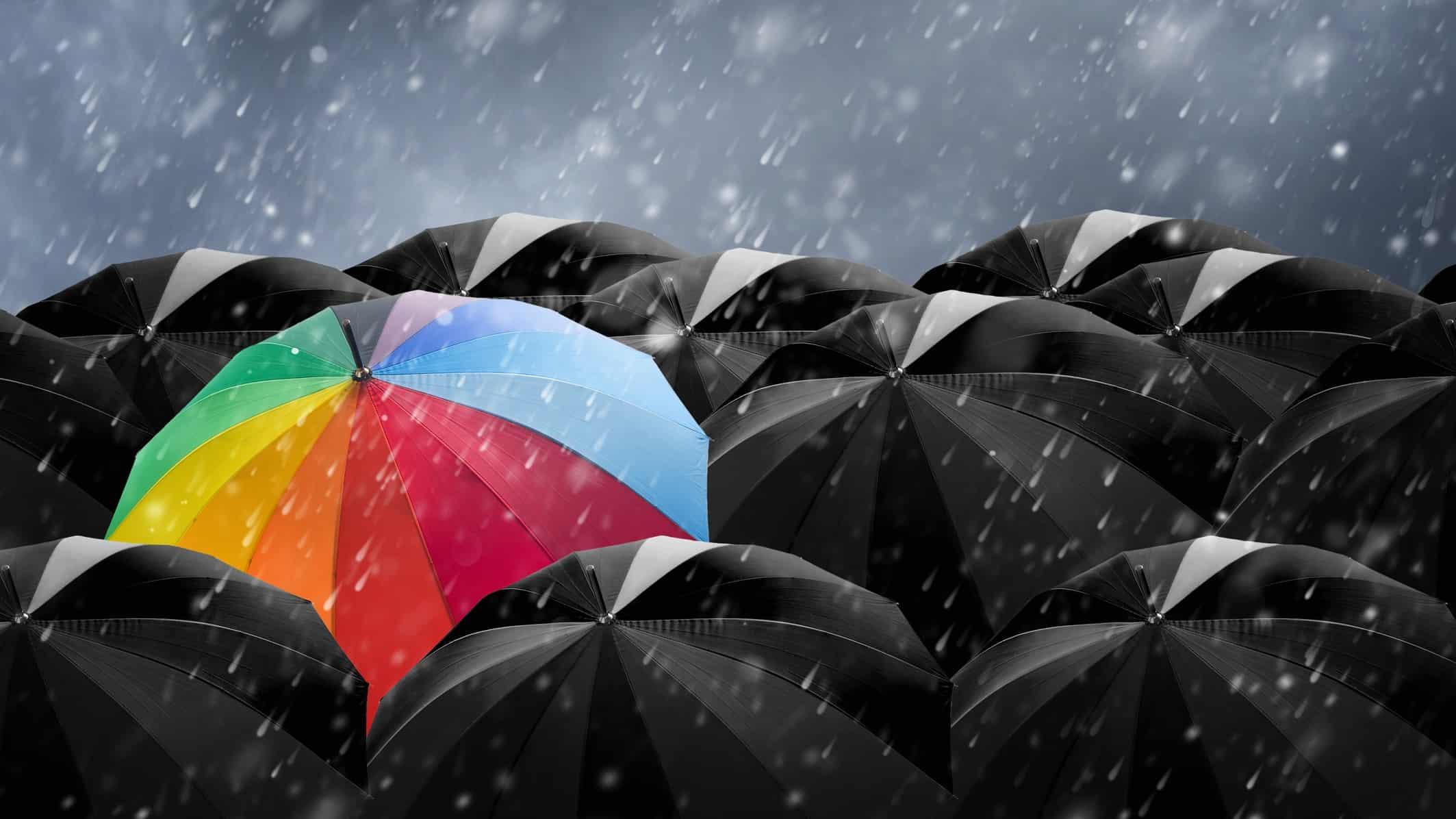 colourful striped umbrella amidst all black umbrellas