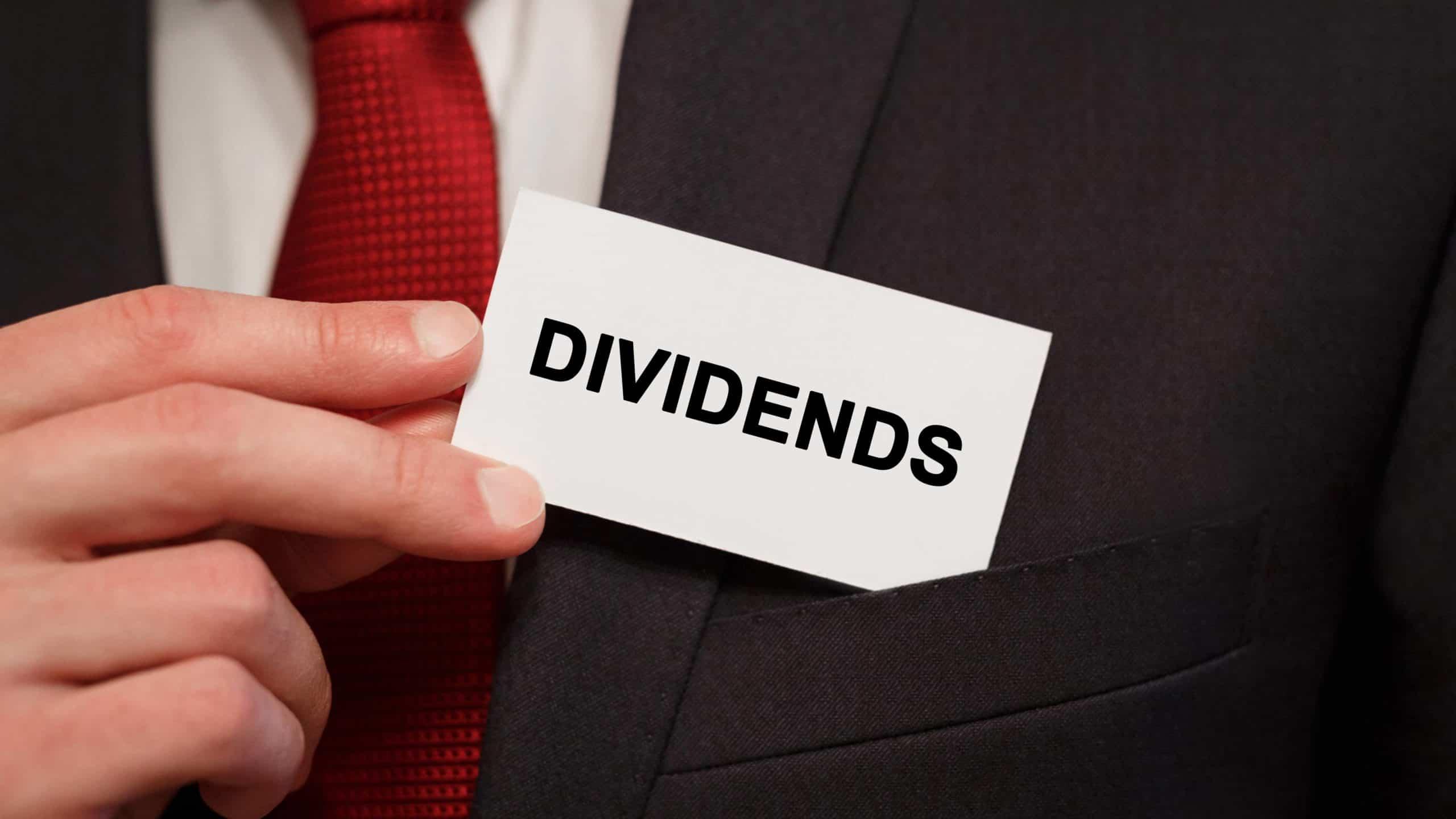 man placing business card in pocket that says dividends signifying asx dividend shares