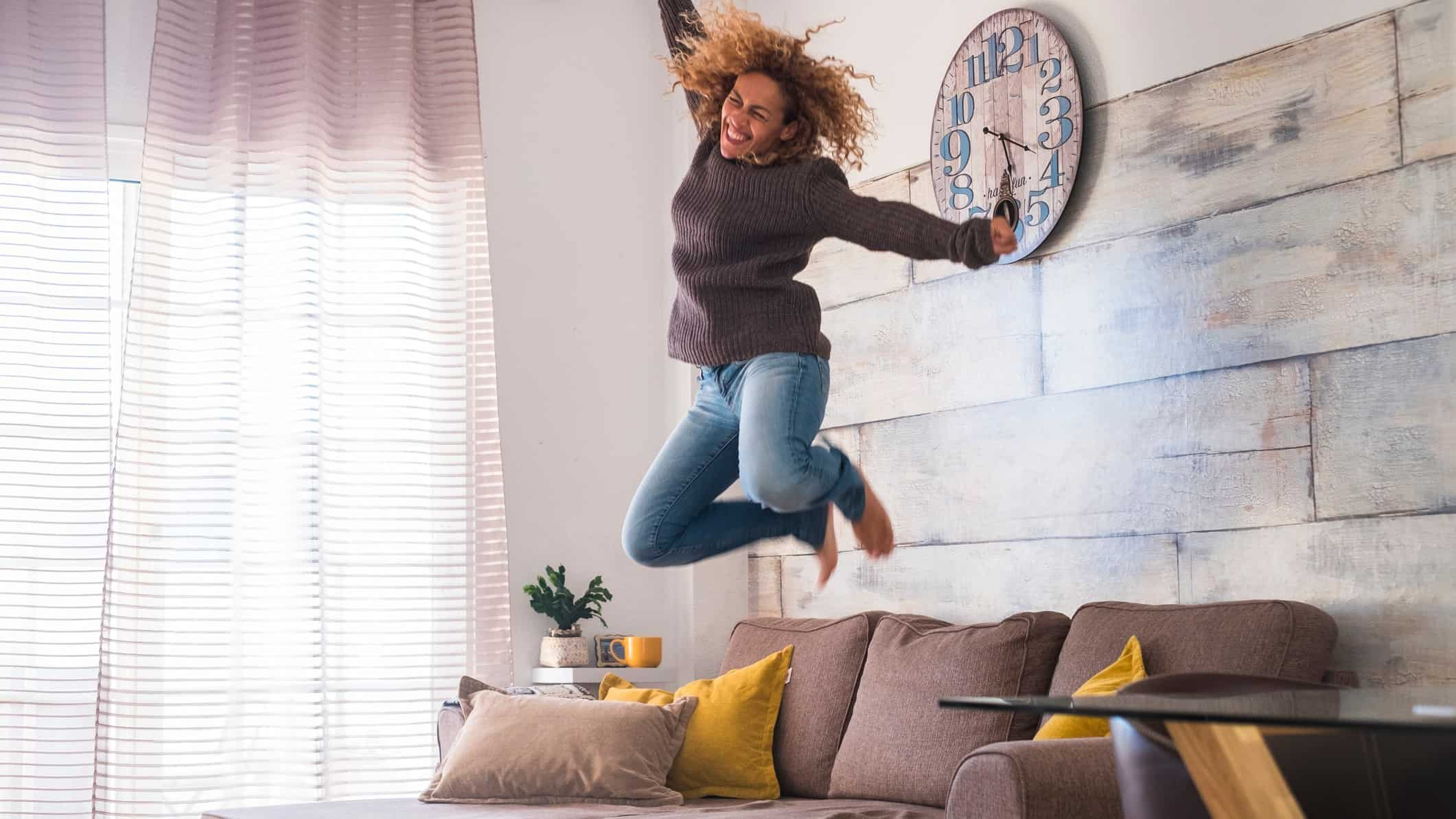 surging asx ecommerce share price represented by woman jumping off sofa in excitement