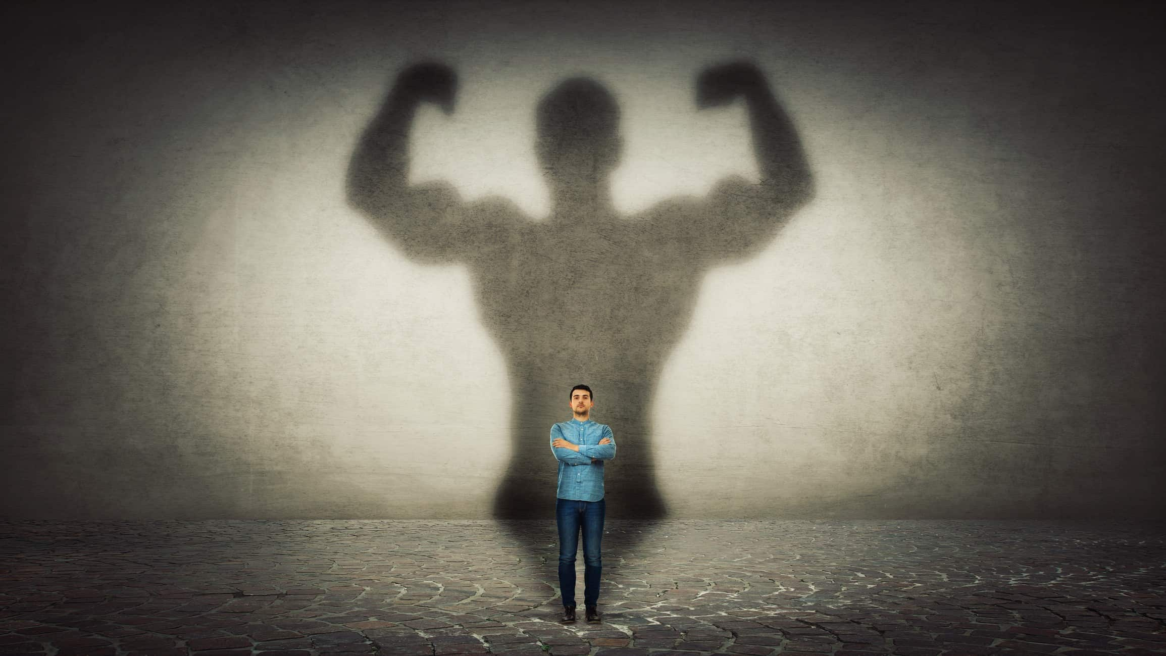 man standing with arms crossed in front of giant shadow of body builder representing asx small cap stocks