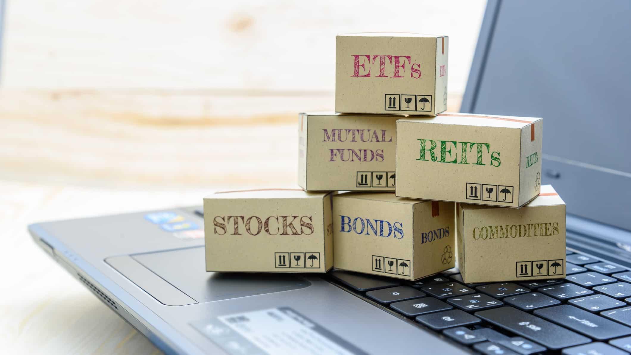 Little boxes entitled ETFs, stocks, REITs and bonds sitting on laptop keyboard