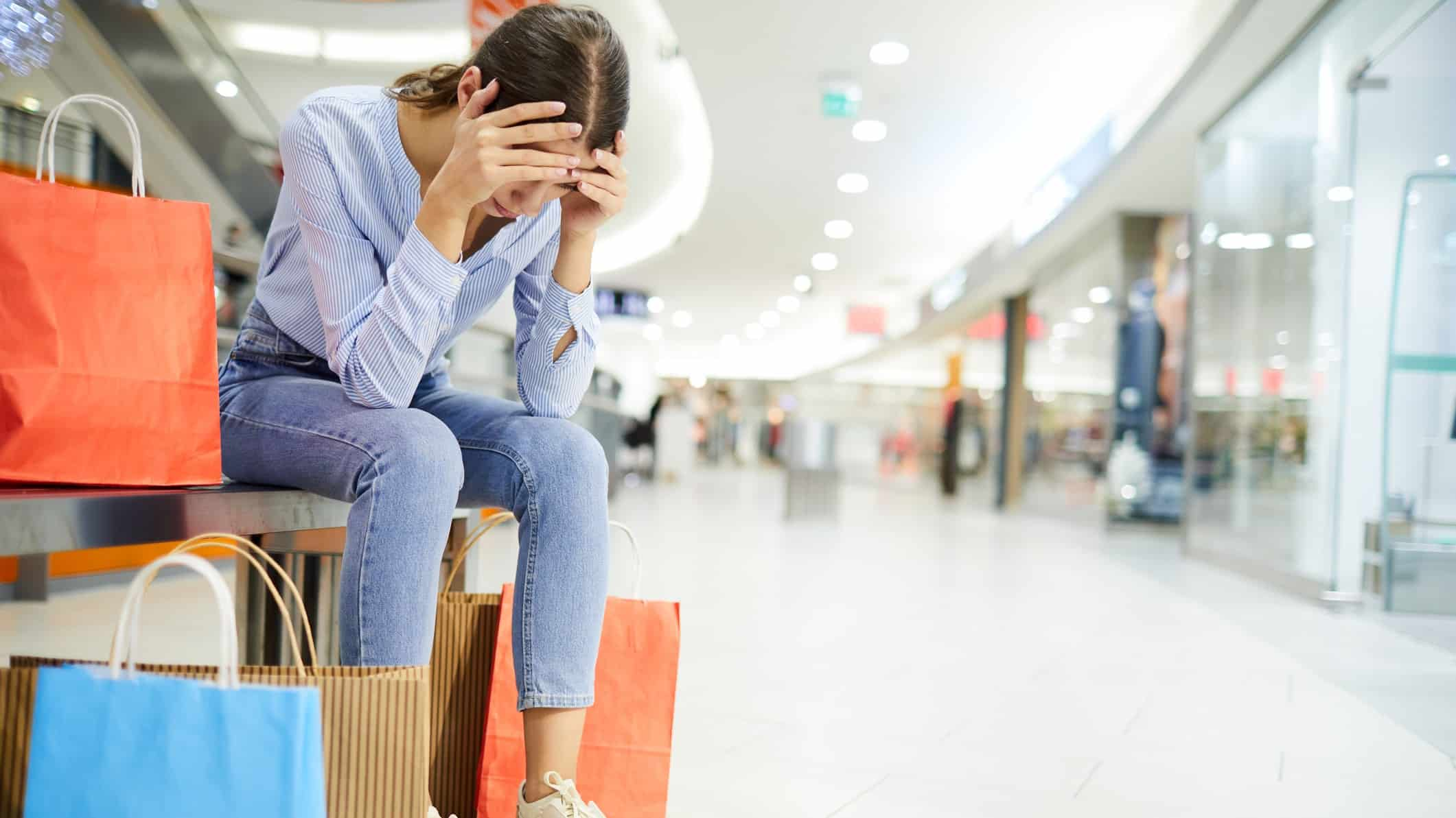 falling asx retail share price represented by sad shopper sitting in mall