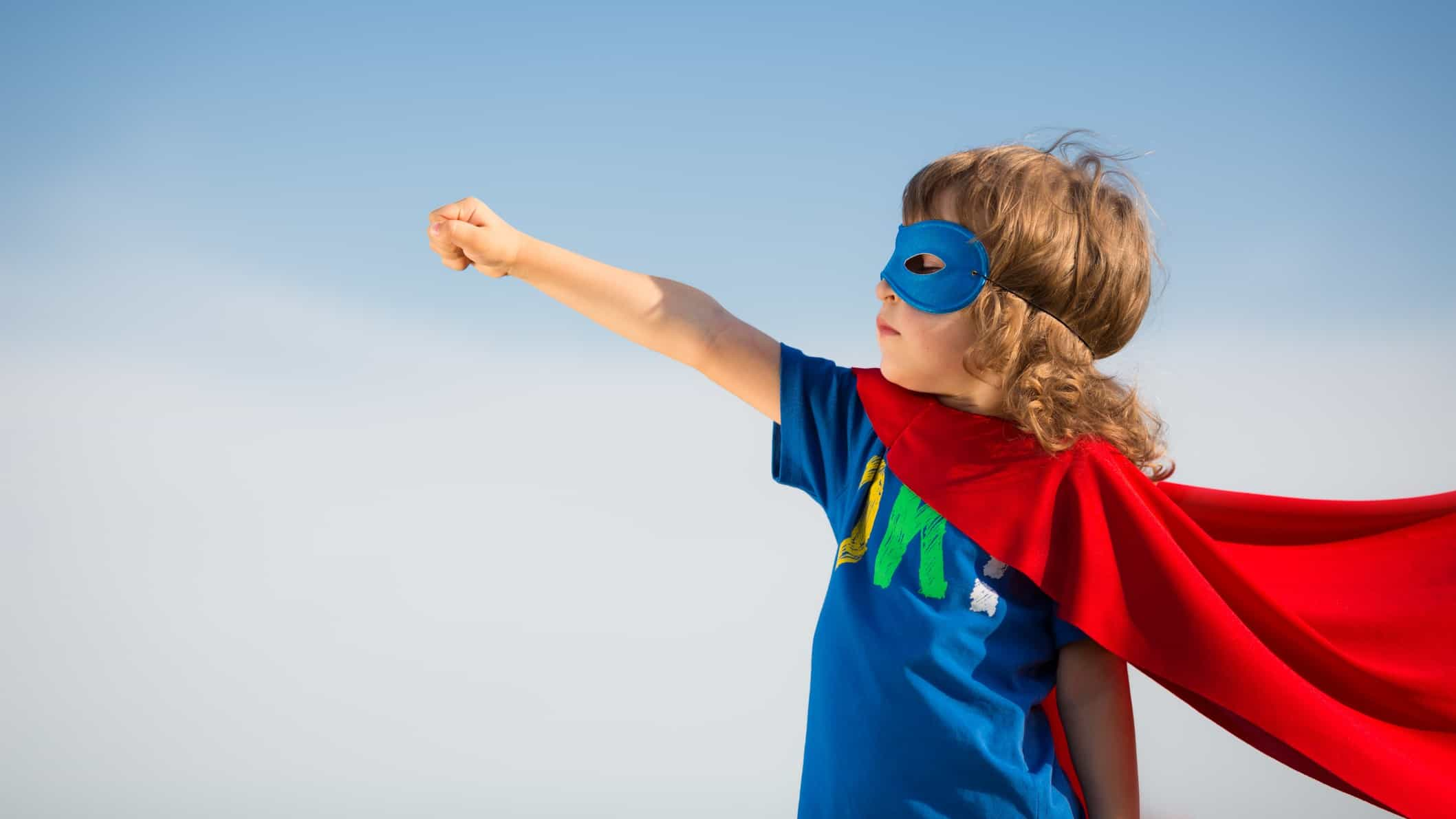 child in superman outfit pointing skyward